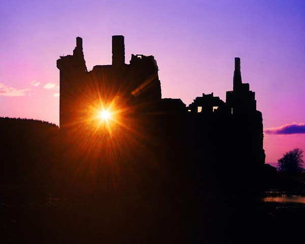Starburst sunset through kilchurn castle ruins loch awe